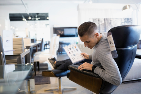 Man shopping for leather chair in home furnishings storeの写真素材 [FYI02310167]