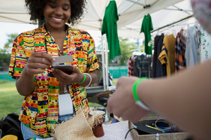 Young woman using credit card reader at vendor booth at summer music festivalの写真素材 [FYI02310300]