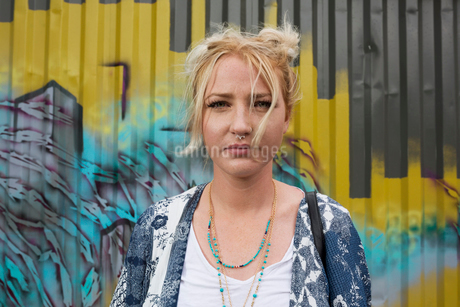 Portrait serious young blonde woman in front of graffiti wallの写真素材 [FYI02310331]