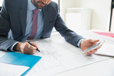 Architect with cell phone reviewing blueprintsの写真素材 [FYI02310373]
