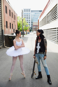 Young ballerina confronting cool skateboarder in urban alleyの写真素材 [FYI02310405]