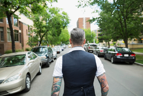 Hipster with tattoos walking down urban streetの写真素材 [FYI02310430]