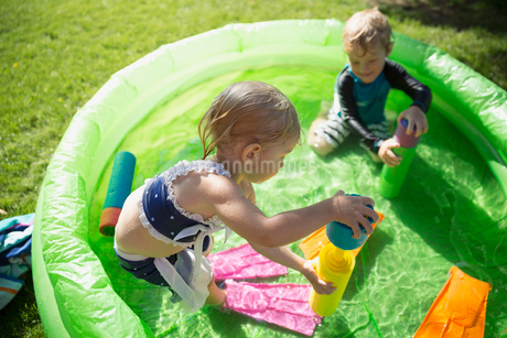 Brother and sister playing with squirt guns in sunny wading poolの写真素材 [FYI02310493]