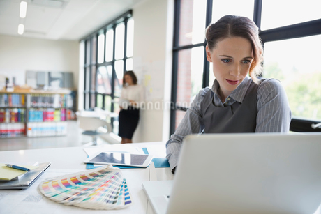 Female designer using laptop next to color swatches in officeの写真素材 [FYI02310610]