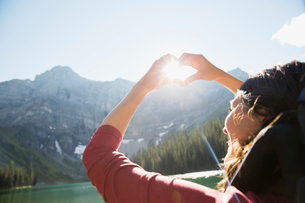 Female hiker gesturing heart-shape against sun at sunny mountain lakesideの写真素材 [FYI02310680]