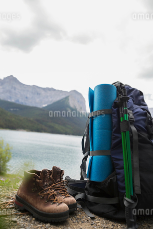 Hiking boots, walking poles, mat and backpack hiking equipment at lakesideの写真素材 [FYI02310806]