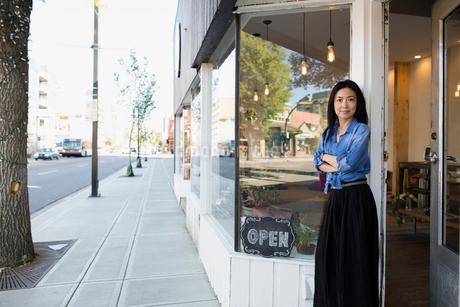 Portrait confident female shop owner in storefront doorwayの写真素材 [FYI02310880]