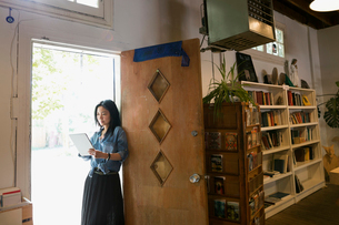 Female shop owner using digital tablet in bookshop doorwayの写真素材 [FYI02310903]