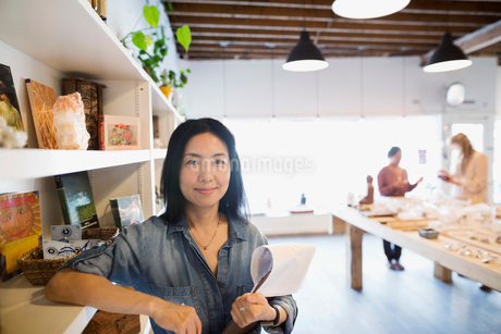 Portrait confident female shop owner with clipboardの写真素材 [FYI02310982]