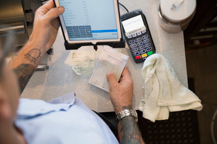 Male cafe owner holding check using digital tablet at cash registerの写真素材 [FYI02311084]