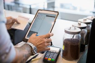 Male cafe owner holding check using digital tablet at cash registerの写真素材 [FYI02311113]