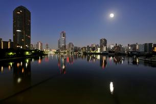 満月の隅田川と深夜の都心のビル群の写真素材 [FYI02311120]