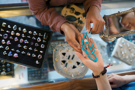 Overhead view women browsing necklace at jewelry counter in shopの写真素材 [FYI02311181]