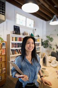 Smiling female shop owner with clipboardの写真素材 [FYI02311185]