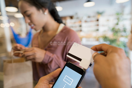 Close up shop owner using contactless payment cell phone credit card readerの写真素材 [FYI02311539]