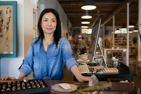 Portrait confident female shop owner at jewelry counterの写真素材 [FYI02311649]
