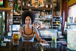 Portrait confident female bartender serving beer behind counterの写真素材 [FYI02311815]