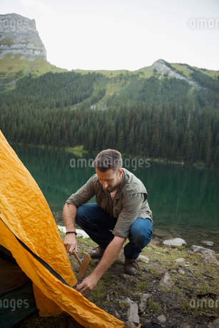 Man pitching tent at remote lakeside campsiteの写真素材 [FYI02311858]