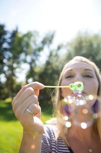 Portrait blonde woman blowing bubbles in sunny summer parkの写真素材 [FYI02311862]