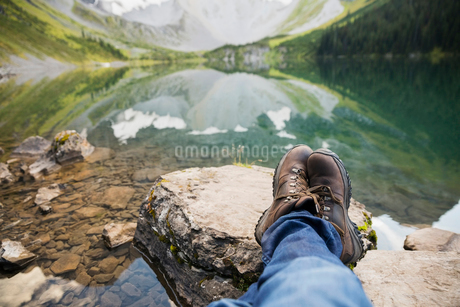 Personal perspective man in hiking boots relaxing with feet up on rocks at remote lakeの写真素材 [FYI02311888]