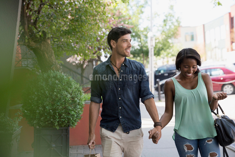 Couple holding hands walking on urban sidewalkの写真素材 [FYI02311933]