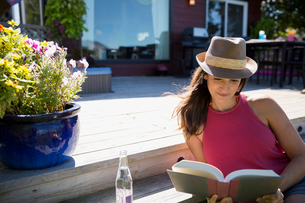 Woman reading book and drinking water on sunny summer patioの写真素材 [FYI02312004]