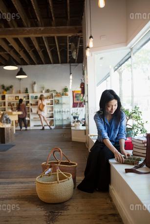 Female shop owner arranging window displayの写真素材 [FYI02312050]