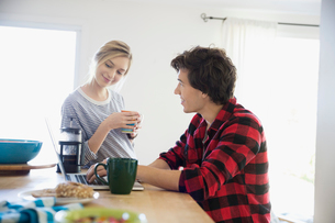 Young couple drinking coffee at laptop in kitchenの写真素材 [FYI02312068]
