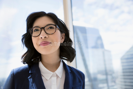 Pensive businesswoman at urban office windowの写真素材 [FYI02312093]