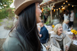 Laughing woman drinking champagne at outdoor dinner partyの写真素材 [FYI02312133]