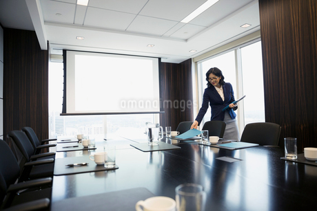 Businesswoman preparing for meeting placing folders on conference room tableの写真素材 [FYI02312202]