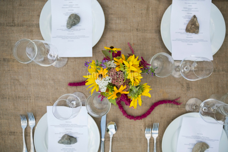 Overhead view of menus under rocks on table at harvest dinner placesettingの写真素材 [FYI02312305]