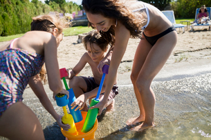Brother and sisters filling squirt guns at sunny summer lakeの写真素材 [FYI02312324]