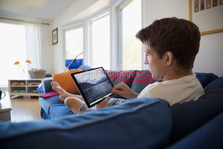 Young man on sofa looking at lake photograph on digital tablet in living roomの写真素材 [FYI02312448]