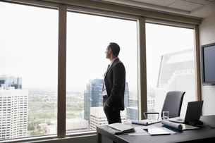 Pensive businessman looking out conference room windowの写真素材 [FYI02312489]