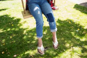 Girl wearing sandals on swing in summer yardの写真素材 [FYI02312605]