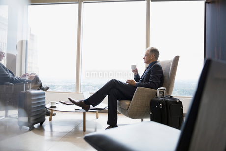 Businessman with luggage drinking coffee in airport loungeの写真素材 [FYI02312627]
