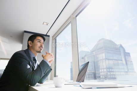 Pensive businessman at laptop looking out urban office windowの写真素材 [FYI02312644]