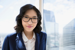 Portrait smiling businesswoman at urban office windowの写真素材 [FYI02312847]