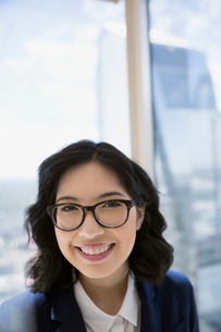 Portrait smiling businesswoman at urban office windowの写真素材 [FYI02312852]