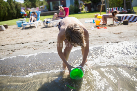 Girl filling bucket with water in sunny summer lakeの写真素材 [FYI02312855]