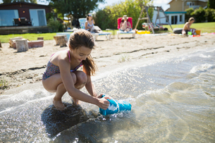 Girl filling bucket with water in sunny summer lakeの写真素材 [FYI02313062]