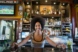 Portrait confident female bartender behind counterの写真素材 [FYI02313110]