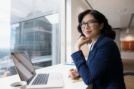 Portrait smiling businesswoman working at laptop in urban office windowの写真素材 [FYI02313153]
