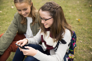 Tween girls texting with cell phone in parkの写真素材 [FYI02313320]