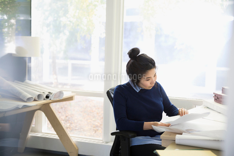 Female architect reviewing paperwork at office deskの写真素材 [FYI02313451]