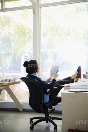 Pensive female architect reviewing blueprints with feet up on office deskの写真素材 [FYI02313473]