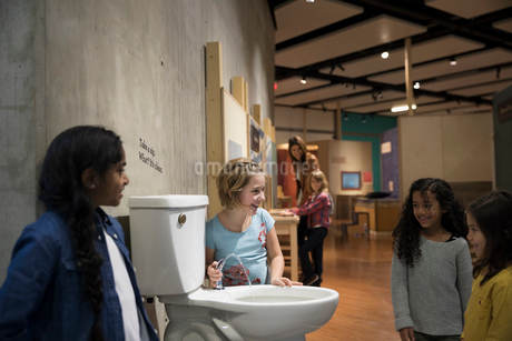 Girls drinking from toilet water fountain in science centerの写真素材 [FYI02313506]