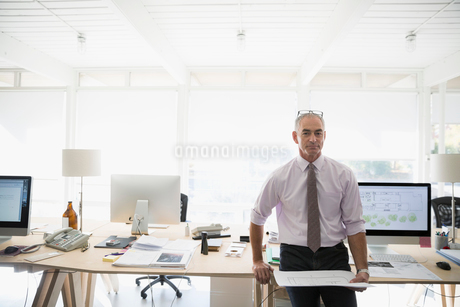 Portrait confident male architect holding blueprint in officeの写真素材 [FYI02313564]