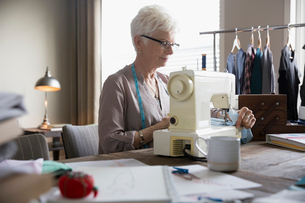 Senior woman seamstress using sewing machine in home officeの写真素材 [FYI02313584]